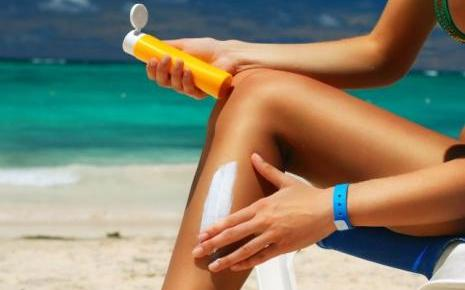7701809091_une-jeune-femme-mettant-de-la-creme-solaire