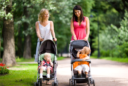Happy mothers walking together with kids in prams